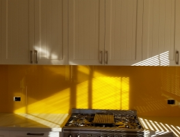 Graphic Glass Services vibrant yellow splashback being installed
