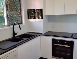 Stunning White Colourback Glass Kitchen Splashback by Graphic Glass Services Qld paired with black accessories
